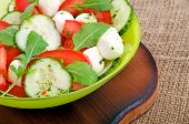 foto of rocket salad  - Fresh salad with mozzarella cheese tomatoes cucumber and rocket salad on the cutting board - JPG