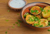 stock photo of oven  - Oven-baked potatoes with herbs on wooden table