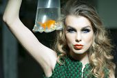 image of little girls photo-models  - Sexy young girl with bright makeup and blonde curly hair holding cellophane package aquarium with goldfish horizontal photo - JPG