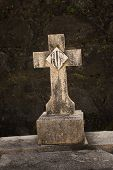 picture of tombstone  - Ancient cross tombstone backed by a dark moldy filled stone wall - JPG