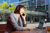 picture of people talking phone  - portrait of a happy business woman talking on mobile phone and working on laptop at outdoor cafe - JPG