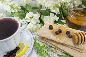 foto of chokeberry  - Healthy breakfast with integral biscuits honey and chokeberry tea - JPG