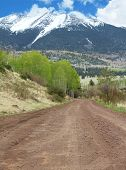 stock photo of dirt road  - Scenic landscape of dirt road with Majestic Snowcapped mountains and aspen trees - JPG