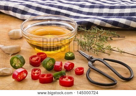 thyme with sliced red and green chili pepper garlic olive oil in a bottle herbs scissors on wooden board