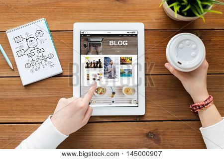 technology, media, internet and people concept - close up of woman with blog web page on tablet pc computer screen, notebook and coffee on wooden table