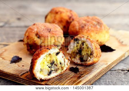 Fried meat patties filled with cheese and fried mushrooms on board and on wooden table. Homemade filled patties prepared from minced Turkey meat. Closeup