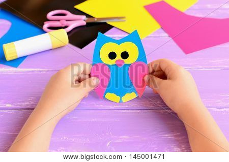 Small child holds paper owl in his hands. Child shows owl crafts. Colored paper sheets, scissors, glue stick on a lilac wooden background. Kids paper crafts. Kids art in kindergarten and at home