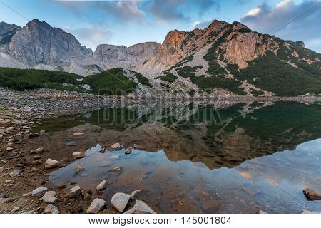 Sunrise with Colored in red rock of Sinanitsa peak and  the lake, Pirin Mountain, Bulgaria