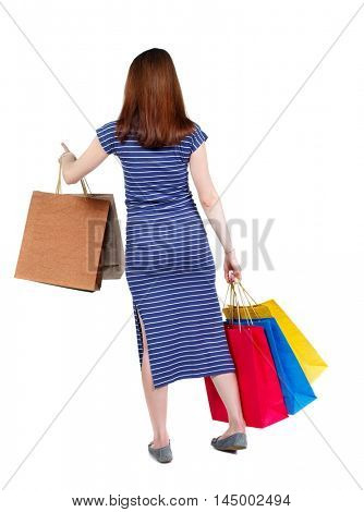 back view of woman with shopping bags pointing . brunette in a blue striped dress presses the button holding shopping bags.