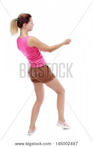 back view of standing girl pulling a rope from the top or cling to something. Isolated over white background. Sport blond in brown shorts pulls the rope side.