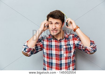 Embarrassed ·irritated young man in checkered shirt taking off headphones over grey background
