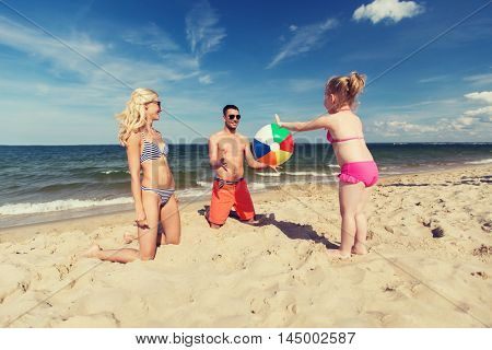 family, travel, vacation and people concept - close up of happy man, woman and little girl playing with inflatable ball on beach