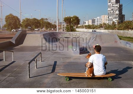 Longboarder In Skate Park With His Dog