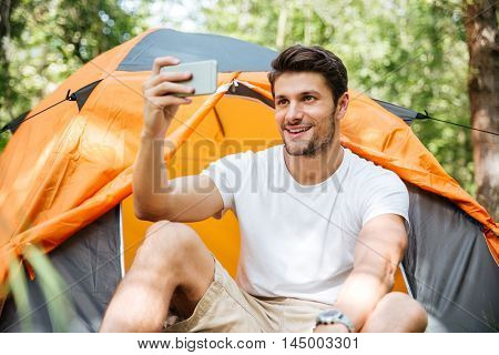 Cheerful young man tourist sitting in touristic tent and taking selfie with mobile phone in forest