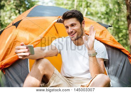 Smiling young man tourist taking selfie with smartphone at touristic tent in forest