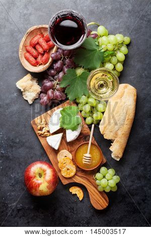 Red and white wine, grape, cheese and honey on stone table. Top view