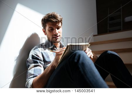 Attractive young man in checkered shirt and jeans sitting on stairs at home and writing in notepad