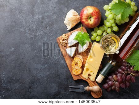 White wine, grape, bread and cheese on stone table. Top view with copy space