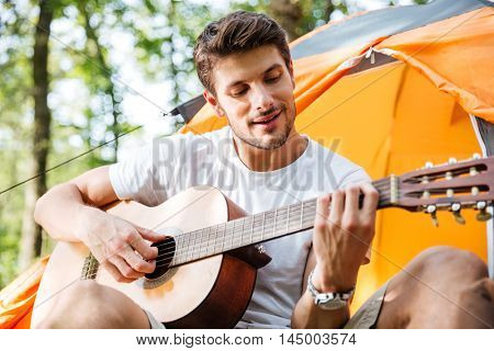 Happy young man tourist sitting in touristic tent and playing guitar in forest