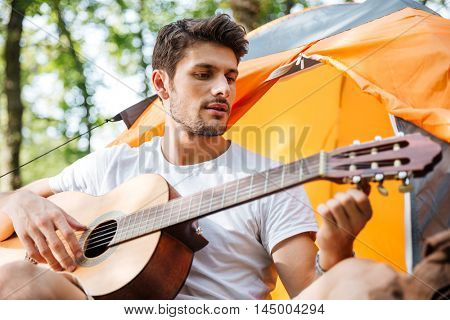 Attractive young man tourist sitting at touristic tent and playing guitar in forest