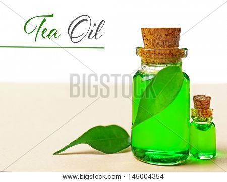 Bottles with tea tree essence and green leaves on table. Space for text.