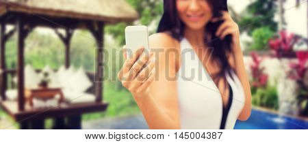 summer, travel, tourism, technology and people concept - close up of sexy young woman taking selfie with smartphone over exotic hotel resort with bungalow and swimming pool background