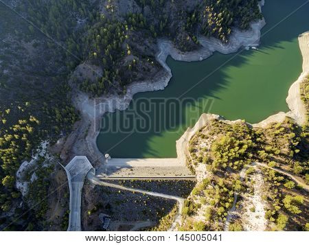 Aerial view of the embankment (earthfill / rockfill) dam in Arminou Paphos Cyprus. A terrain reservoir of the river Diarizos in Pafos cutting through the green valley and lush forest of laona mountain leading to the Venetian bridge.
