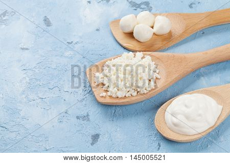 Dairy products spoons over stone table. Sour cream, cheese and curd.