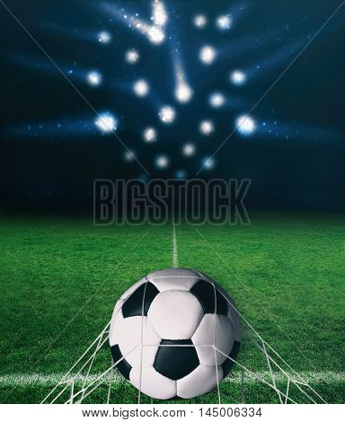 Soccer ball on a green grass on dark background and spotlight with laser rays