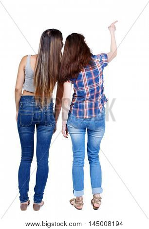 Back view of two pointing young girl. Rear view people collection. backside view of person. Two young girls in jeans are pointing to the sky with his finger.