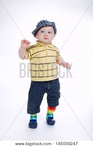 little funny boy in gumboots isolated on white