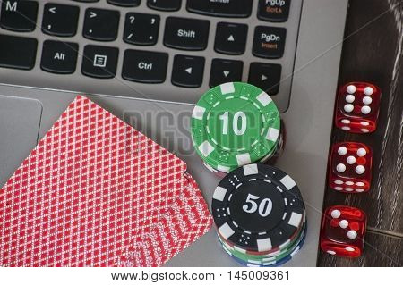 Gambling chips, poker card and red dice on laptop keyboard background