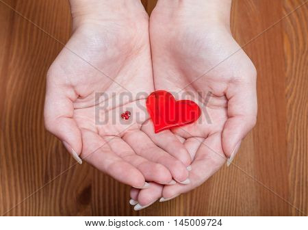 little and big hearts in female hands with wooden background