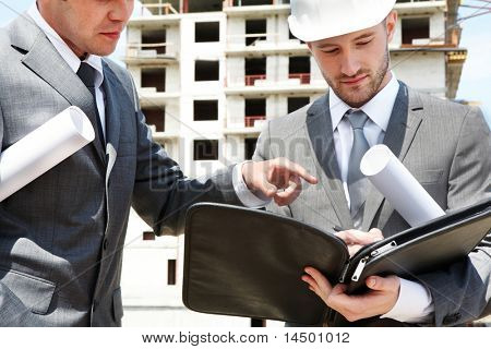 Portrait of two builders standing at building site and discussing new project held by one of them