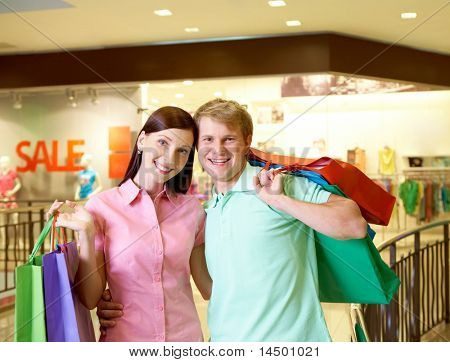 Retrato de shopaholics segurando paperbags e sorrindo para a câmera