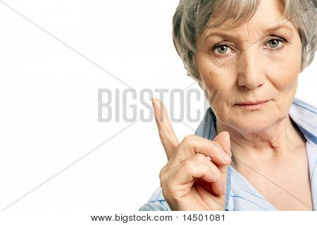 Photo of elderly female with her forefinger pointed upwards on white background