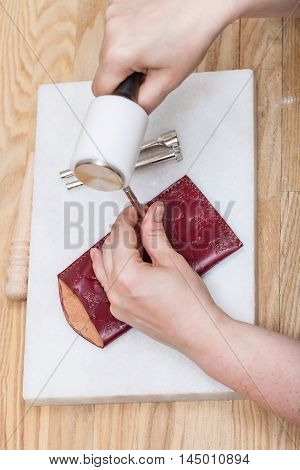 Craftsman Corrects Stamping Of Leather Pouch