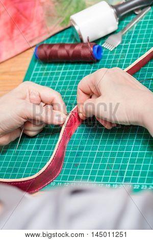 Craftsman Sews Belt For New Leather Bag