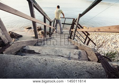 Young Man Stands On Old Wooden Stairway