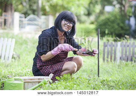asian woman relaxing happiness emotion planting organic vegetable in home garden