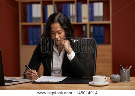 Indonesian concentrated female lawyer checking business contract