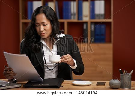 Indonesian business lady drinking coffee and reading document