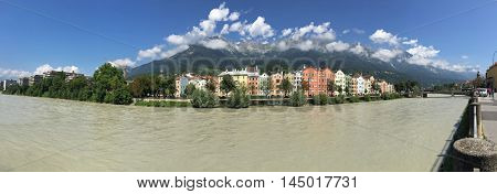 Panoramic view of colorful buildings and mountains along Inn river in Innsbruck city. Panorama of capital of Austria, Europe during summer time. Inn River is a right tributary of the Danube