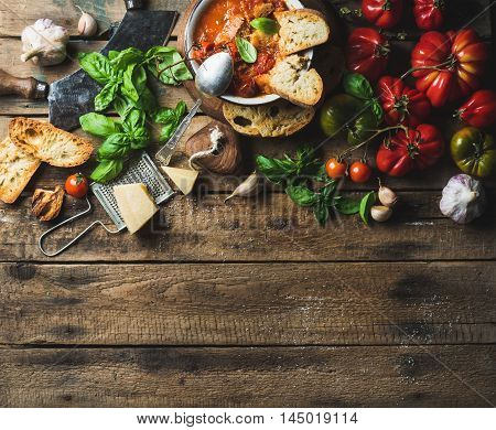 Homemade Italian roasted tomato and garlic soup in bowl with basil and Parmesan cheese over old rustic wood background, top view, copy space, horizontal composition