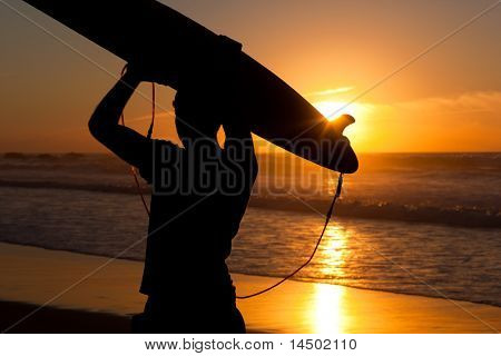 Young surfer on the beach with his surf board over the head, looking at the ocean