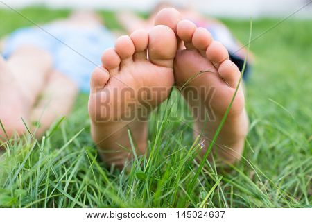 Group of happy children feet lying on green grass outdoors in summer park