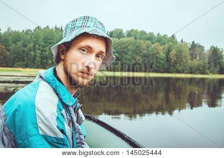 Fisherman in action. Bearded young man with panamku cap from a boat relaxing and fishing in a lake outdoor weekend on nature. Concept camping Holiday. The Republic of Karelia Ladoga Lake Russia.