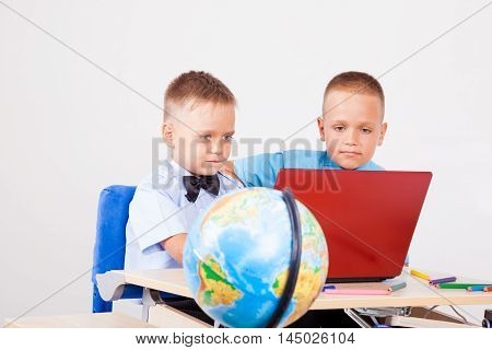 two boys sitting at the computer in school with globe