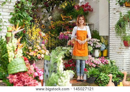 Young lovely florist working her flower shop