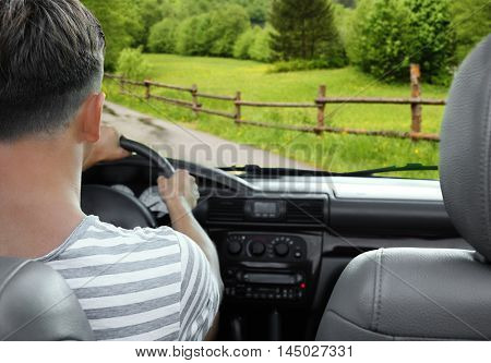 Man driving car. View from car windshield to road and forest.